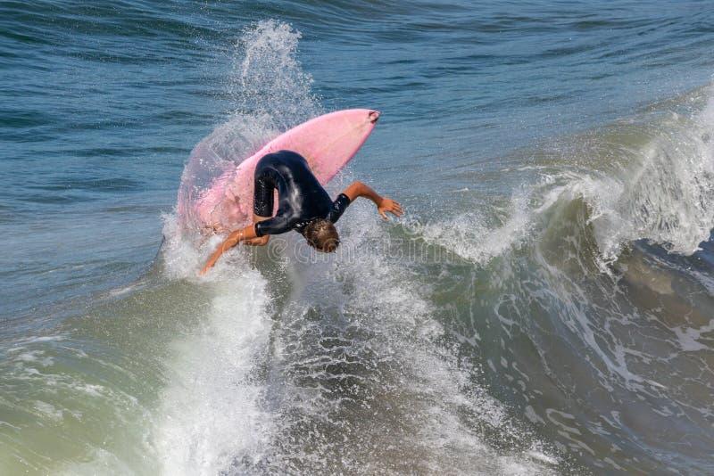 Surfista na prancha do pnk sobre uma onda imagens de stock royalty free