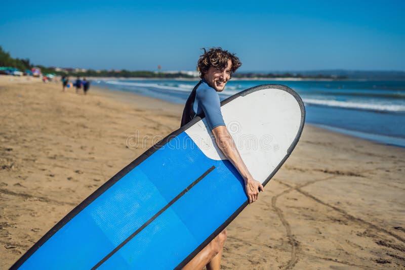 Surfista novo desportivo considerável que levanta com sua prancha sob o seu imagens de stock royalty free