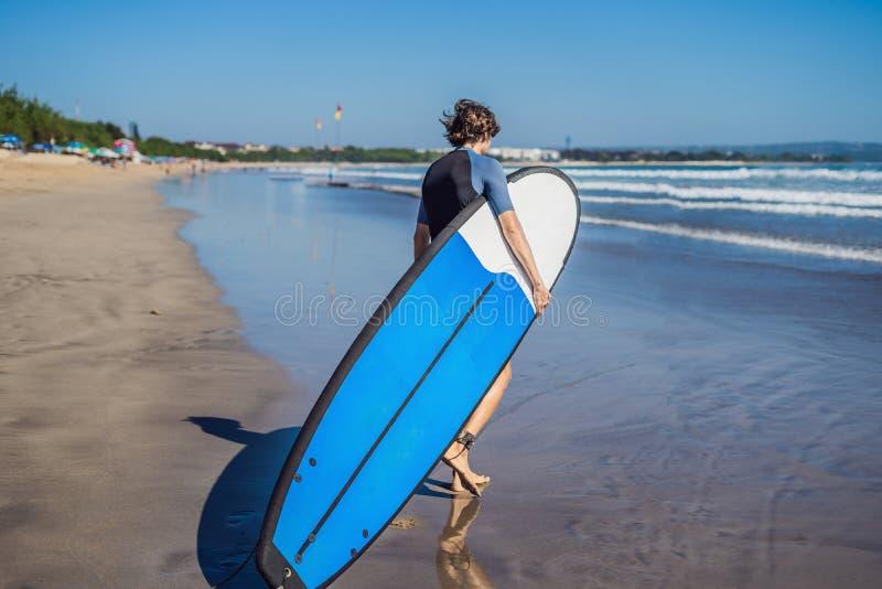 Surfista novo desportivo considerável que levanta com sua prancha sob o seu imagem de stock royalty free