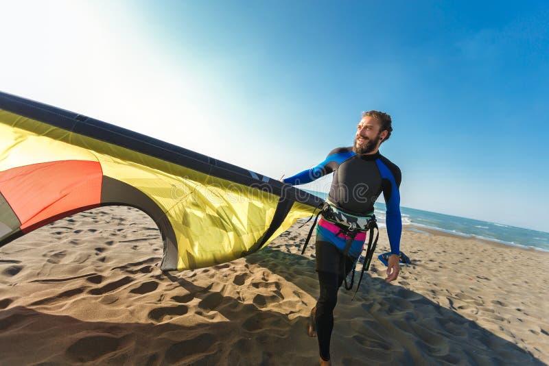 Surfista profissional do homem caucasiano que está no Sandy Beach com seu papagaio imagens de stock royalty free