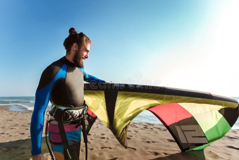 Surfista profissional do homem caucasiano que está no Sandy Beach com seu papagaio fotografia de stock royalty free