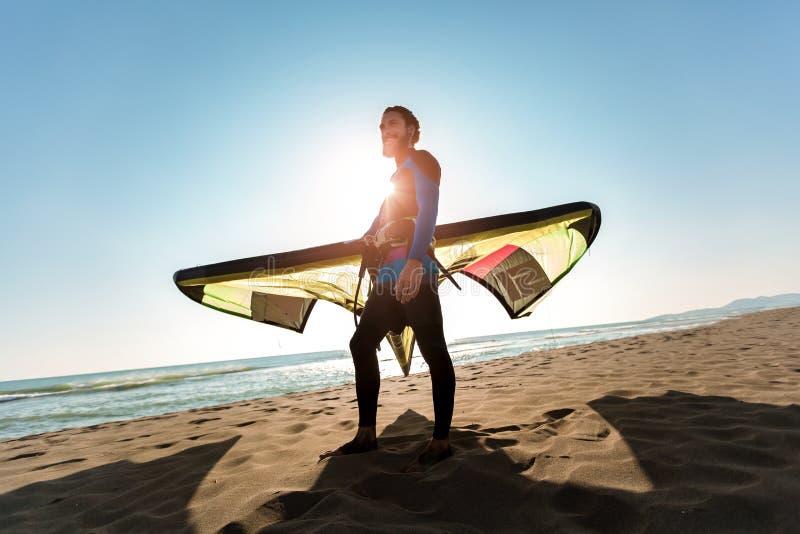 Surfista profissional do homem caucasiano que está no Sandy Beach com seu papagaio fotos de stock