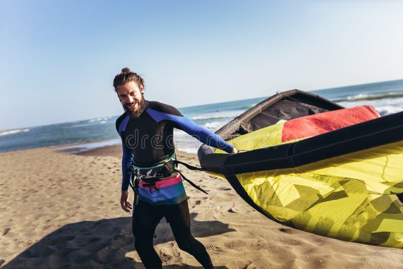 Surfista profissional do homem caucasiano que está no Sandy Beach com seu papagaio imagem de stock royalty free