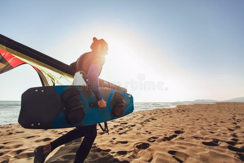 Surfista profissional do homem caucasiano que está no Sandy Beach com seus papagaio e placa foto de stock royalty free