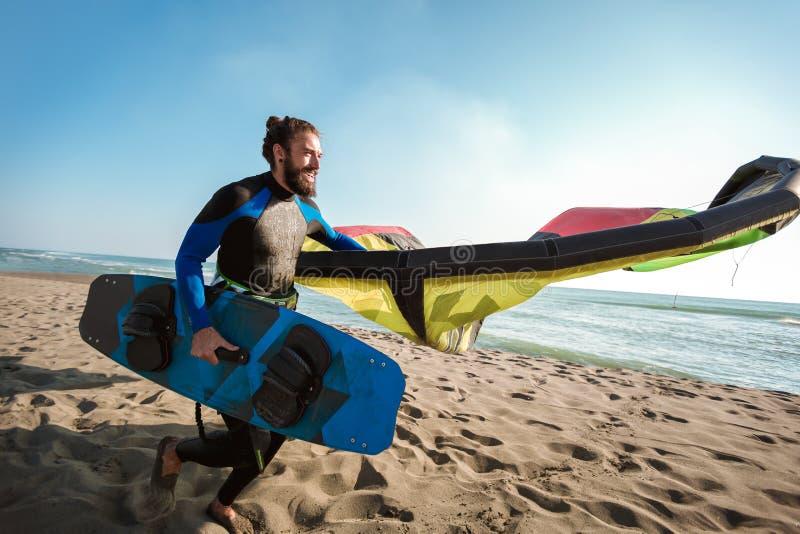 Surfista profissional do homem caucasiano que está no Sandy Beach com seus papagaio e placa imagens de stock royalty free