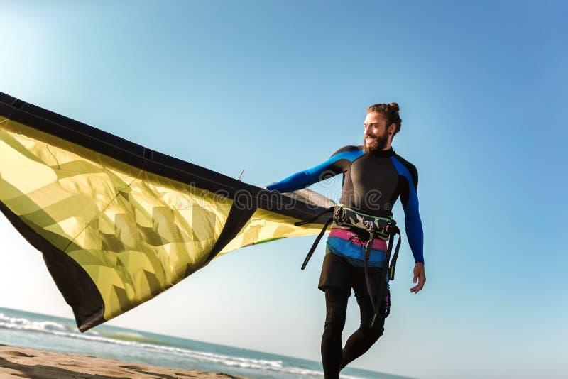 Surfista profissional do homem caucasiano que est? no Sandy Beach com seu papagaio fotografia de stock