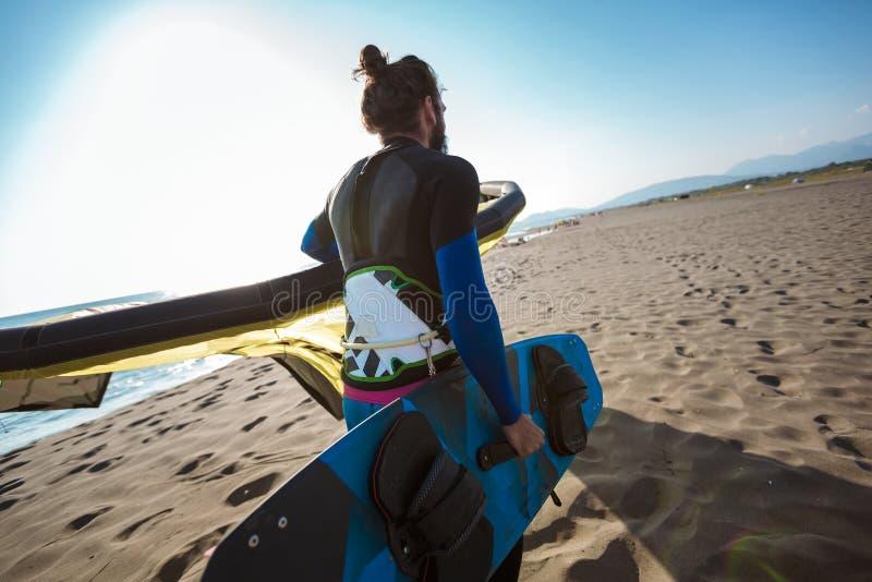 Surfista profissional do homem caucasiano que est? no Sandy Beach com seus papagaio e placa imagem de stock royalty free