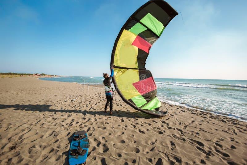 Surfista profissional do homem caucasiano que est? no Sandy Beach com seus papagaio e placa foto de stock royalty free