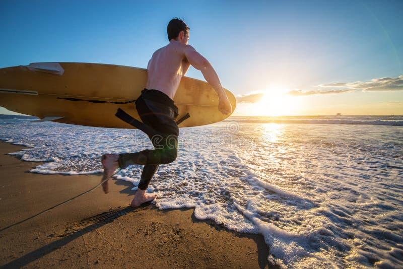 Surfista que corre no oceano imagens de stock
