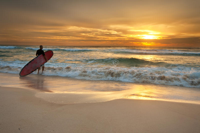 Surfista que entra no oceano no nascer do sol fotografia de stock
