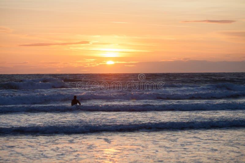 Surfista sulla spiaggia dell'oceano al tramonto fotografia stock libera da diritti