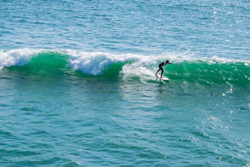 Surfista in una muta umida che equilibra sul suo bordo di spuma mentre guidando una piccola onda nell'oceano Pacifico verde blu fotografia stock