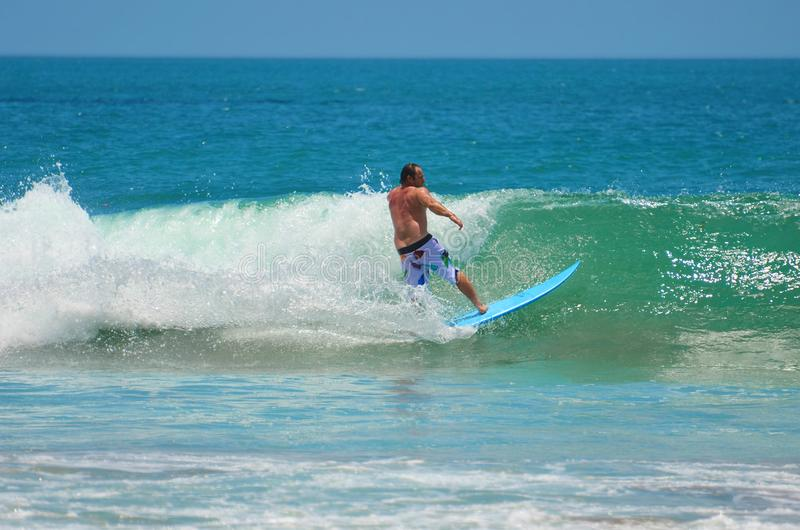 Surfista in verde blu nell'onda di oceano, praticante il surfing L'Indonesia, Bali, il 10 novembre 2011 immagini stock