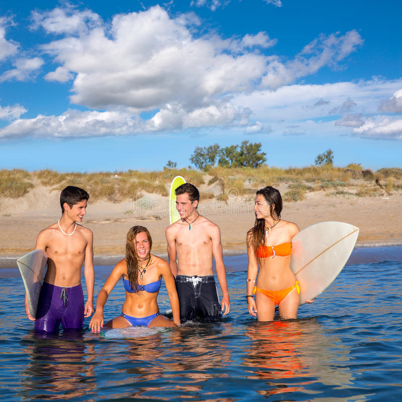 Surfistas adolescentes bonitos felizes que apreciam na praia fotografia de stock royalty free