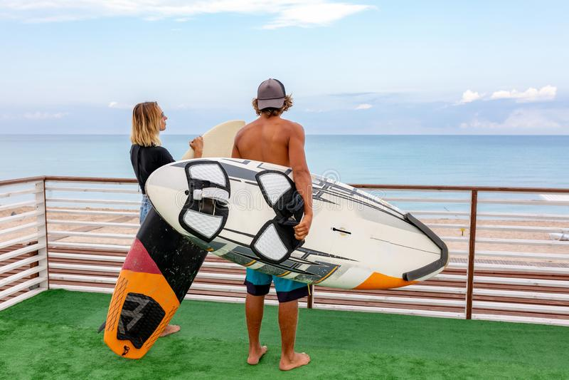 Surfistas ativos novos de sorriso dos pares que relaxam na praia após o esporte com prancha Estilo de vida saudável Água extrema imagem de stock royalty free