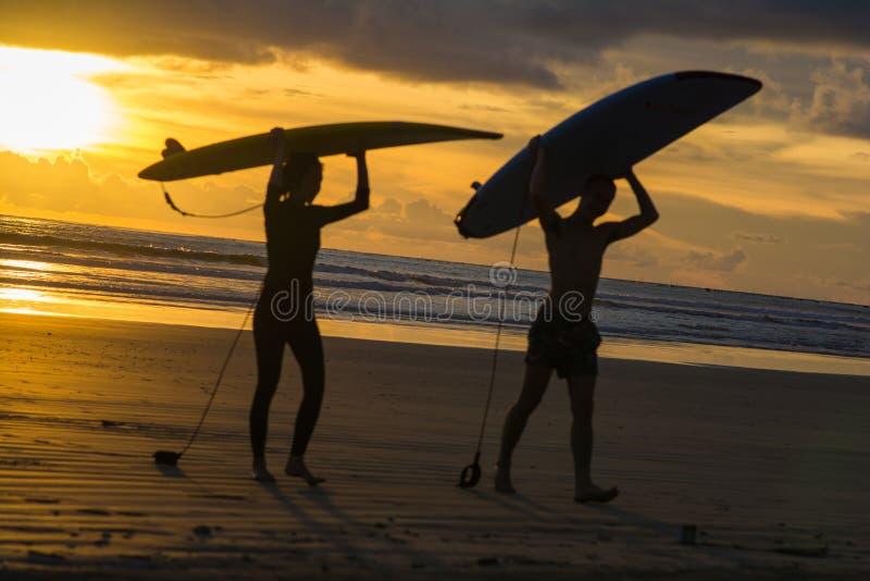 Surfistas com a prancha na praia no por do sol fotografia de stock royalty free