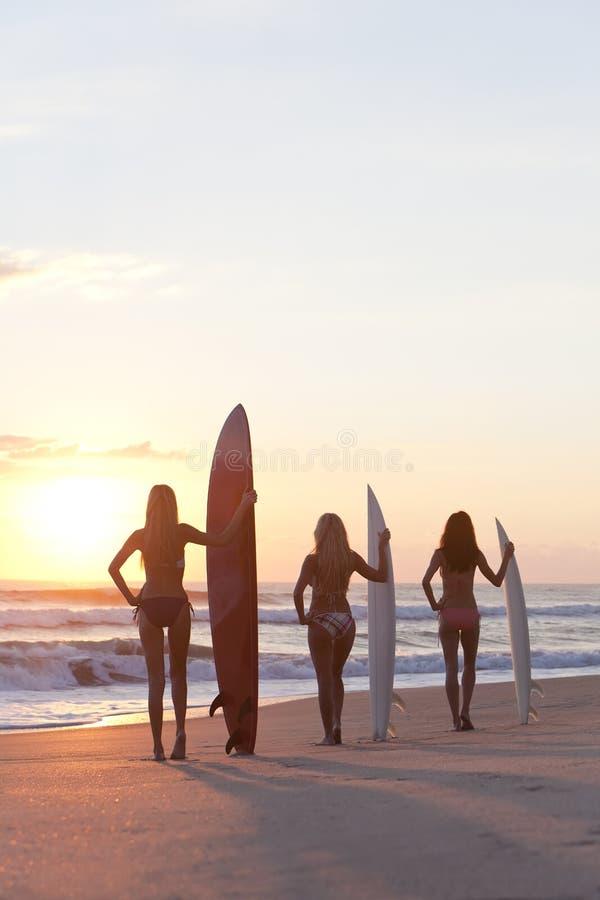 Surfistas das mulheres com as prancha no por do sol imagens de stock royalty free