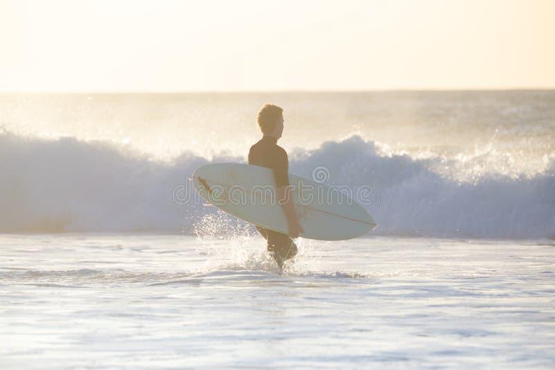 Surfistas na praia com prancha imagens de stock