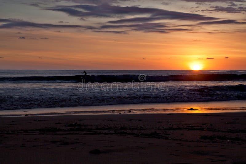 Surfistas na praia de Santa Teresa no por do sol/Costa Rica foto de stock