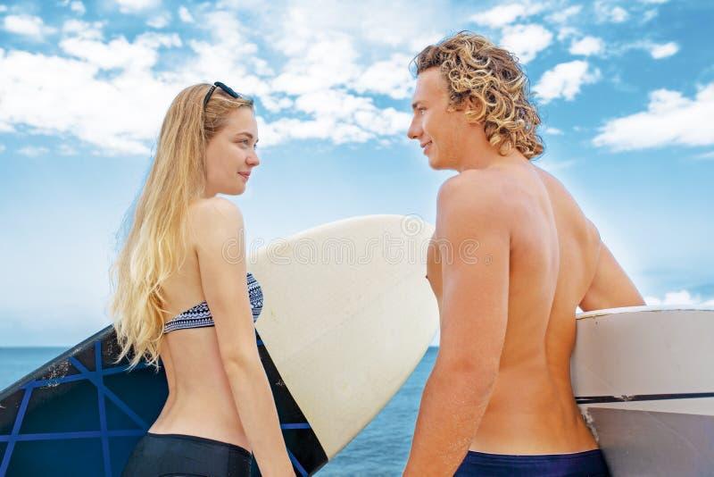 Surfistas nos pares de sorriso da praia de surfistas que andam na praia e que têm o divertimento no verão Esporte extremo e imagens de stock