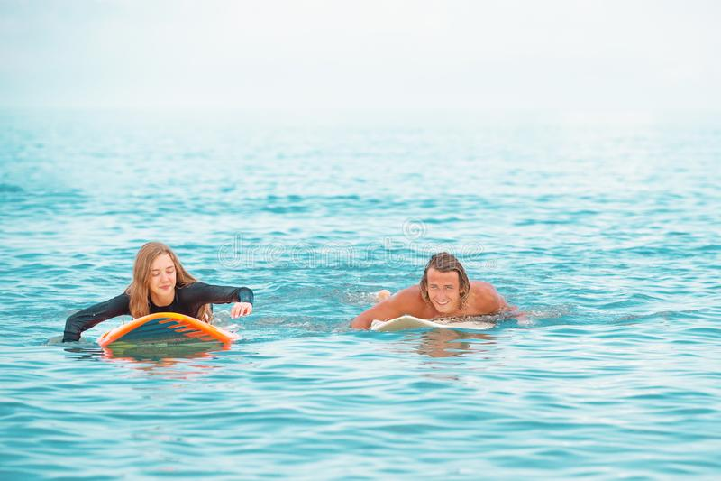 Surfistas nos pares de sorriso da praia de surfistas que nadam e que têm o divertimento no verão Conceito extremo do esporte e da imagem de stock royalty free