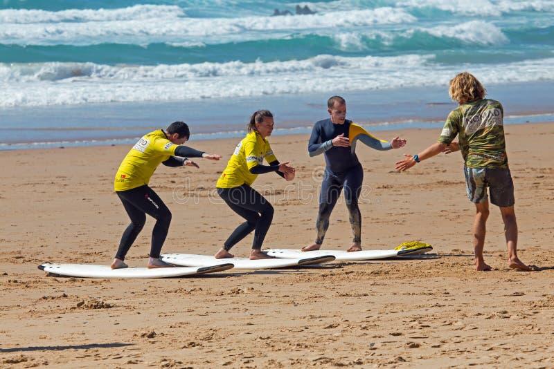 Surfistas que obtêm lições surfando no vale Figueiras do Praia em Portugal fotos de stock royalty free