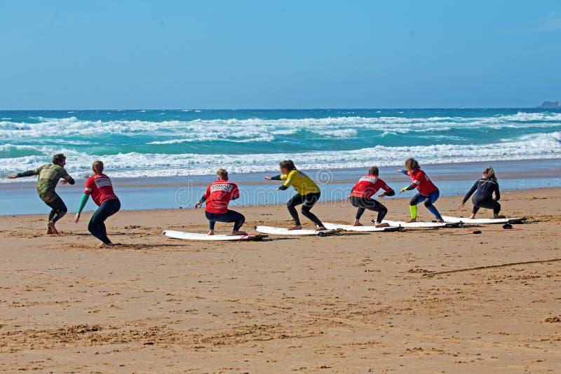 Surfistas que obtêm lições surfando no vale Figueiras do Praia em Portugal foto de stock