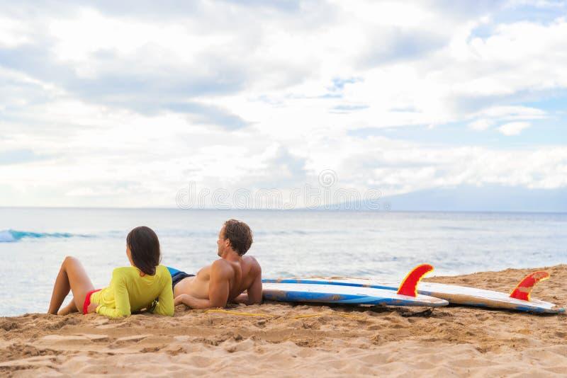 Surfistas surfando dos pares que relaxam na praia de Havaí imagens de stock