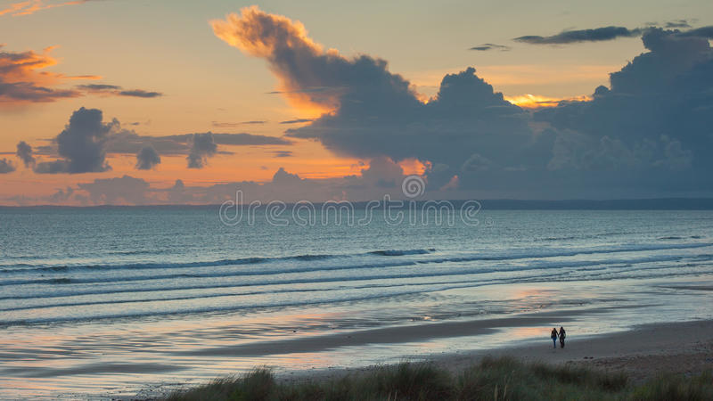 Surfisti che camminano avanti e che perfino spiaggia con un tramonto dietro loro immagine stock libera da diritti