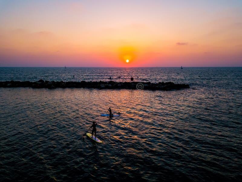 Surfisti del SUP che remano con il tramonto immagini stock libere da diritti