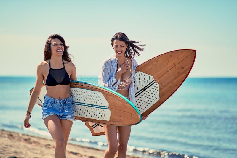 Surfisti delle donne che camminano sulla spiaggia e che si divertono di estate Vaca fotografie stock libere da diritti