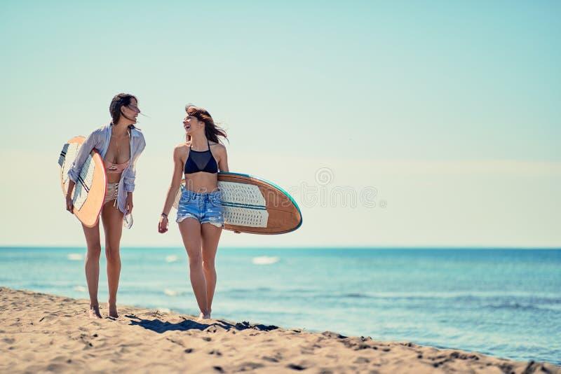 Surfisti sulla spiaggia divertendosi di estate Ragazze con una spuma b fotografie stock libere da diritti