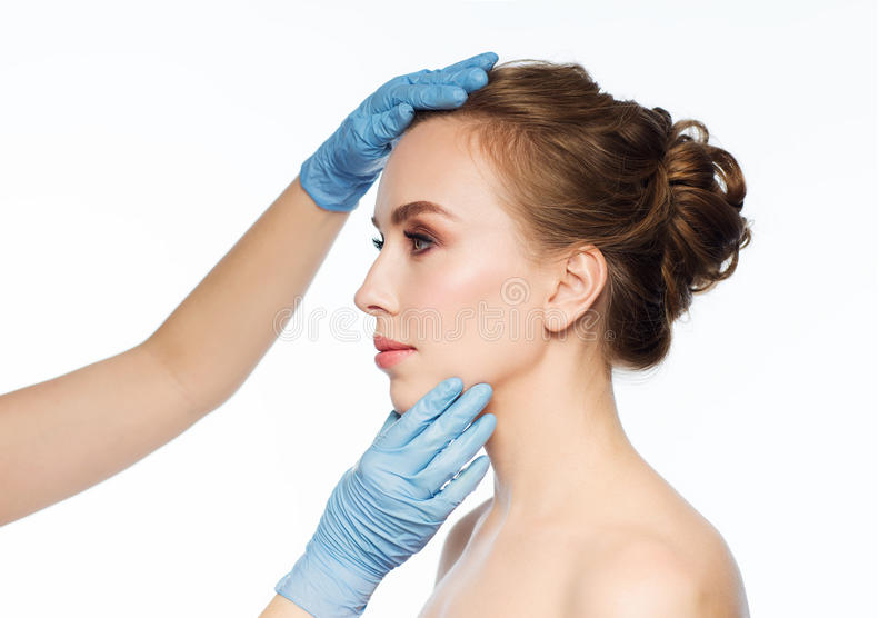 Surgeon or beautician hands touching woman face royalty free stock photos