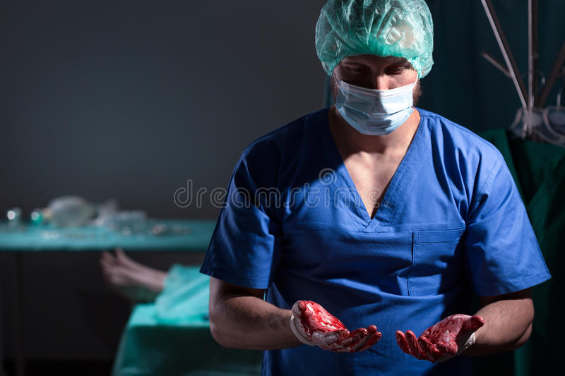 Surgeon with bloody hands stock photo