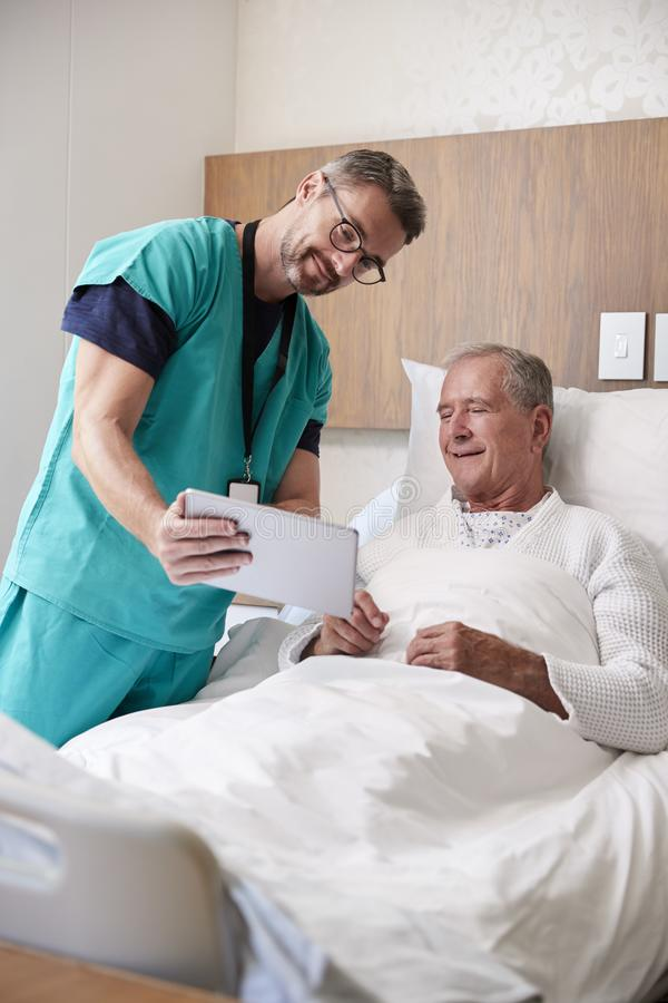 Surgeon With Digital Tablet Visiting Senior Male Patient In Hospital Bed In Geriatric Unit royalty free stock photo