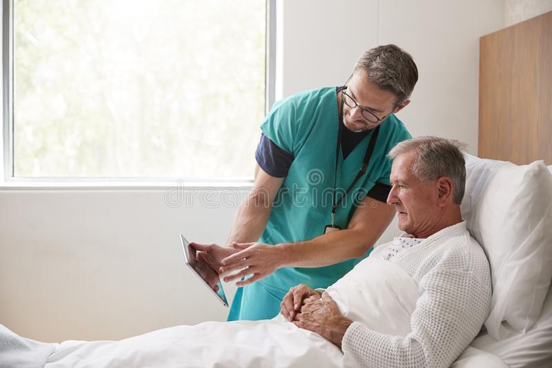 Surgeon With Digital Tablet Visiting Senior Male Patient In Hospital Bed In Geriatric Unit royalty free stock photography