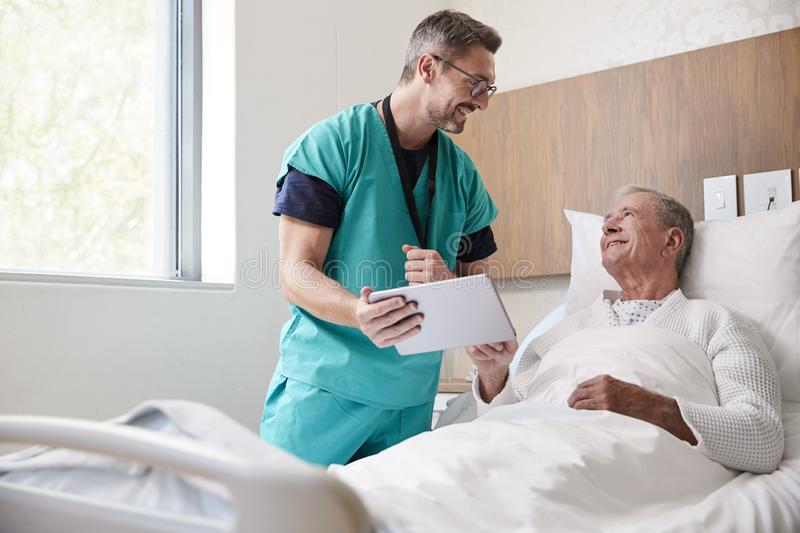 Surgeon With Digital Tablet Visiting Senior Male Patient In Hospital Bed In Geriatric Unit stock photography