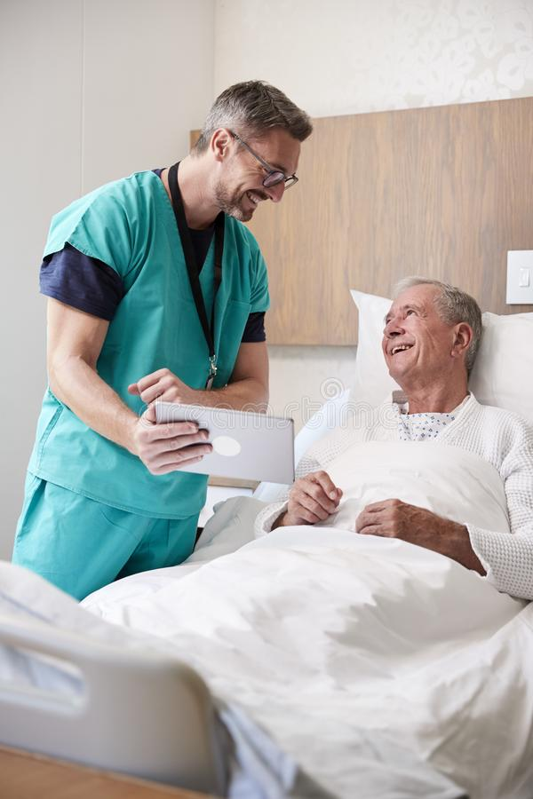 Surgeon With Digital Tablet Visiting Senior Male Patient In Hospital Bed In Geriatric Unit stock images