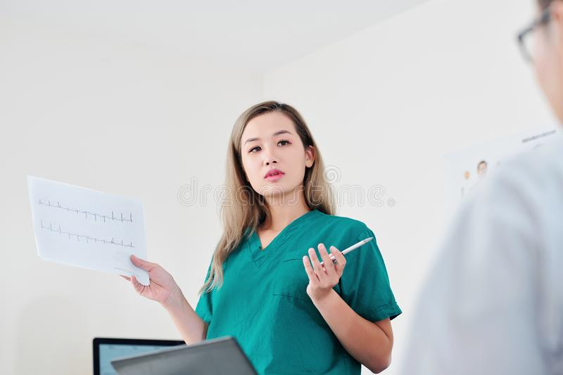 Surgeon discussing patient cardiogram royalty free stock images