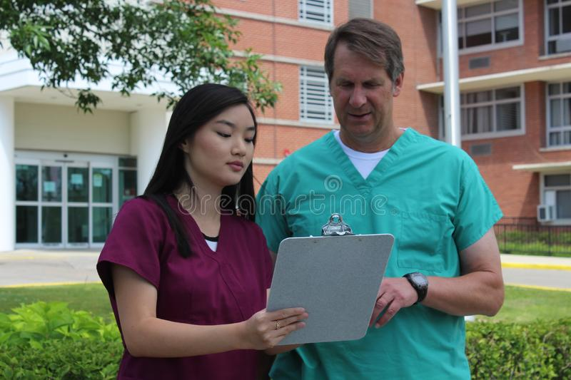 Surgeon or Doctor or Physician or Clinician and Asian Nurse Stand in Front of Hospital Discussing Patient Chart. Surgeon, physician, doctor, clinician and Asian stock image