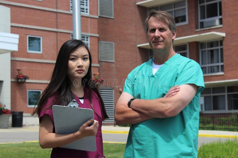 Surgeon, Doctor, Physician, Clinician and Asian Nurse Wearing Scrubs Stand in Front of Hospital. Surgeon, doctor, physician, or clinician and Asian nurse holding royalty free stock photos