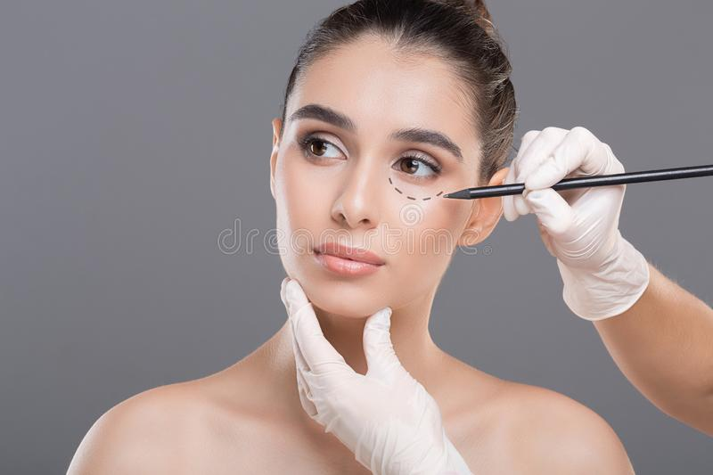Surgeon drawing marks on female face against gray background. Plastic surgery concept stock image