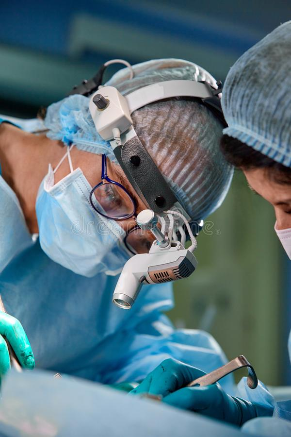 Surgeon and his assistant performing cosmetic surgery on nose in hospital operating room. Nose reshaping, augmentation royalty free stock photos