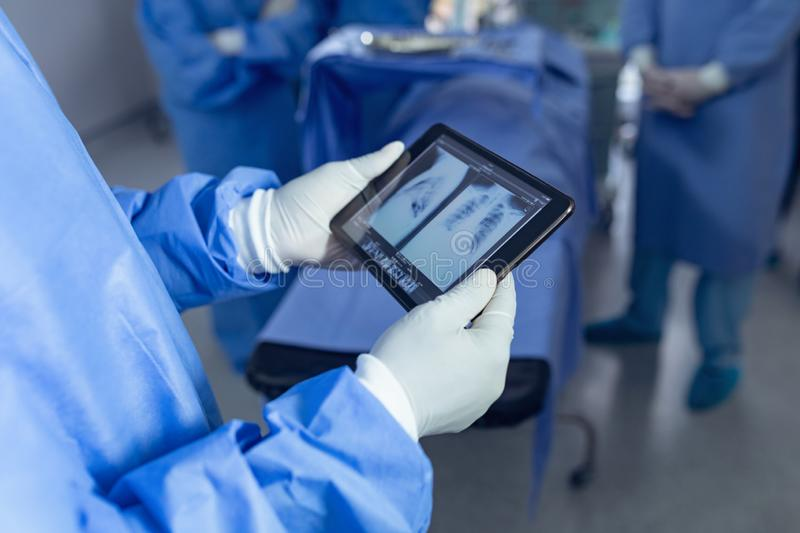 Surgeon looking x-ray report on digital tablet in operating room at hospital. Mid section of African american surgeon looking x-ray report on digital tablet in stock photo