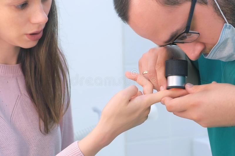 Surgeon and patient examine wart on finger using dermatoscope magnifier. Surgeon and patient women examine wart on finger of using dermatoscope magnifier before stock photos