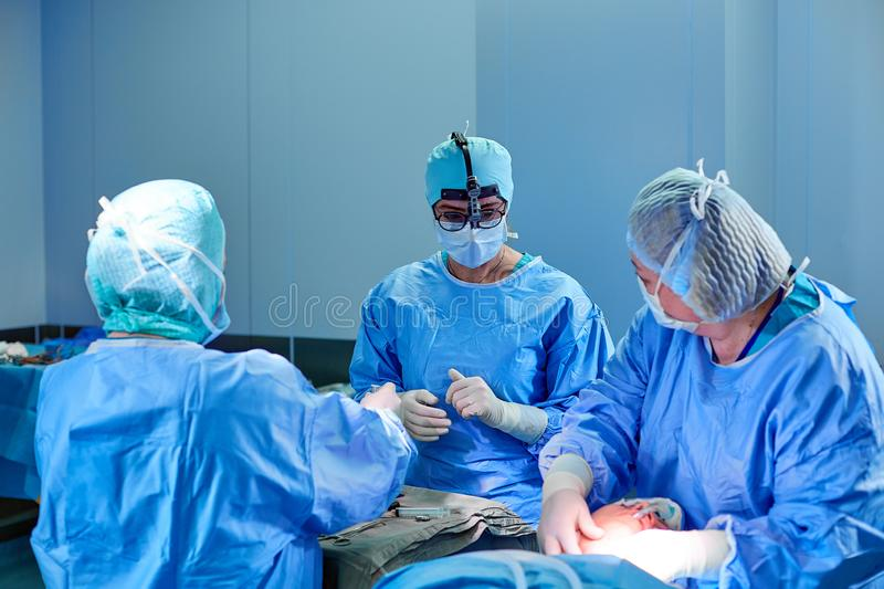 Surgeon performing cosmetic surgery in hospital operating room. Surgeon in mask wearing loupes during medical procadure stock image