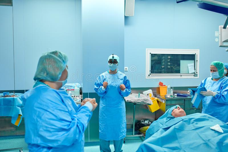 Surgeon performing cosmetic surgery in hospital operating room. Surgeon in mask wearing loupes during medical procadure royalty free stock photography