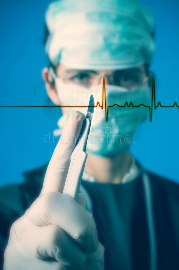 Surgeon with scalpel. Surgeon with a scalpel. Pulse graph in foreground. Focus on scalpel royalty free stock photography