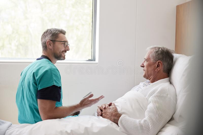 Surgeon Visiting And Talking With Senior Male Patient In Hospital Bed In Geriatric Unit stock photo