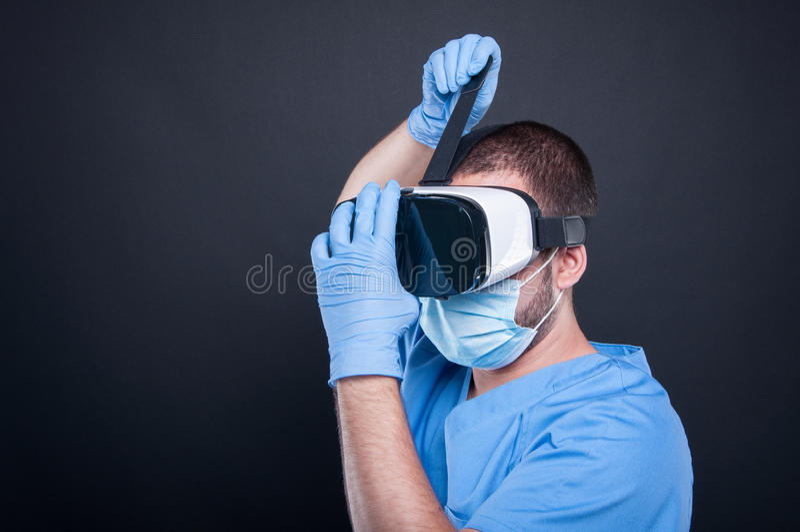 Surgeon wearing scrubs putting on vr goggles stock photos